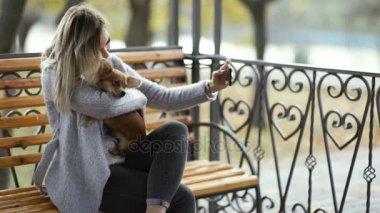 fiatal gyönyörű nő nem selfie a parkban a vicces Hosszúszőrű Csivava kutyájával. Őszi háttér