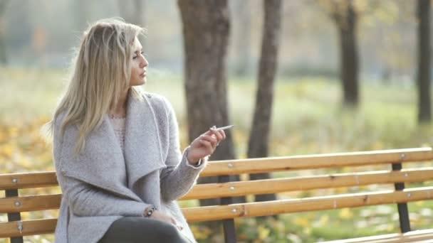 fiatal szép üzletasszony cigarettázott a parkban. Őszi háttér