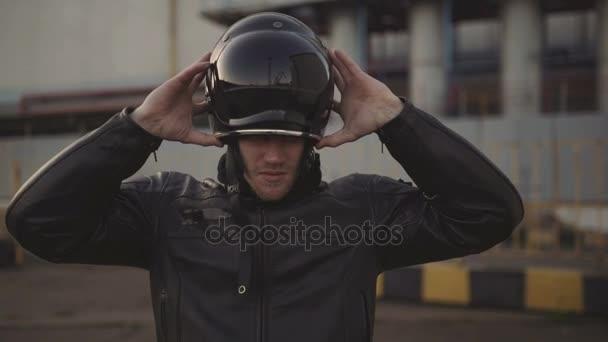 mladý atraktivní muž motocyklista se svou helmu a vlastní motocykl na ulici