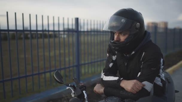 mladá atraktivní motocyklista s černou helmu na ulici. Muž Motocykl biker
