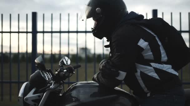 fiatal, vonzó motoros fekete sisak utcában. Ember motorkerékpár-motoros