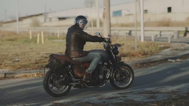 Muž na koni starý motocykl vlastní café-racer na lesní silnici při západu slunce. Stabilní záběr