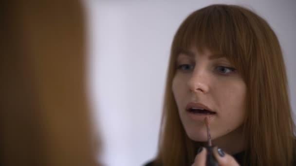 Compongono lapplicazione, LUCIDALABBRA, rossetto. Ritratto di giovane ragazza red-haired attraente per le labbra, primo piano. Donna di bellezza make-up