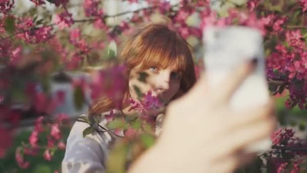 krásná mladá zrzavá žena mezi Kvetoucí třešeň sakura stromu jarní růžové květy takže selfie na smartphone na západ slunce