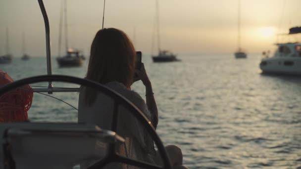 Krásná žena na jachtě fotí při západu slunce v zátoce Cala Saona. Luxusní jachta v blízkosti ostrova Formentera