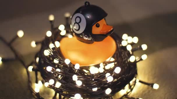 Close-up shot of rubber duck in hand made motorcycle helmet on background of christmas garland