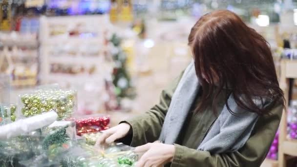 Mladá krásná žena chodí po obchodě a vybírá vánoční dekorace a dekorace na oslavu Nového roku. Nový rok nakupování