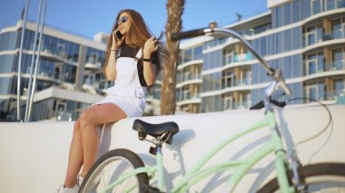 Young attractive woman uses a smartphone and riding vintage bike near the sea during sunrise or sunset
