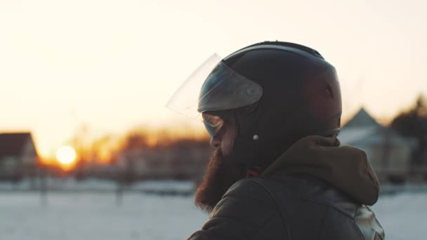 Portrait of a man motorcyclist in a black helmet at sunset on snow field. Man rides a motorcycle in cold winter