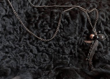 bijouterie. the necklace lies on a black sheep skin. contrast. the stones shimmer from the natural sun color.