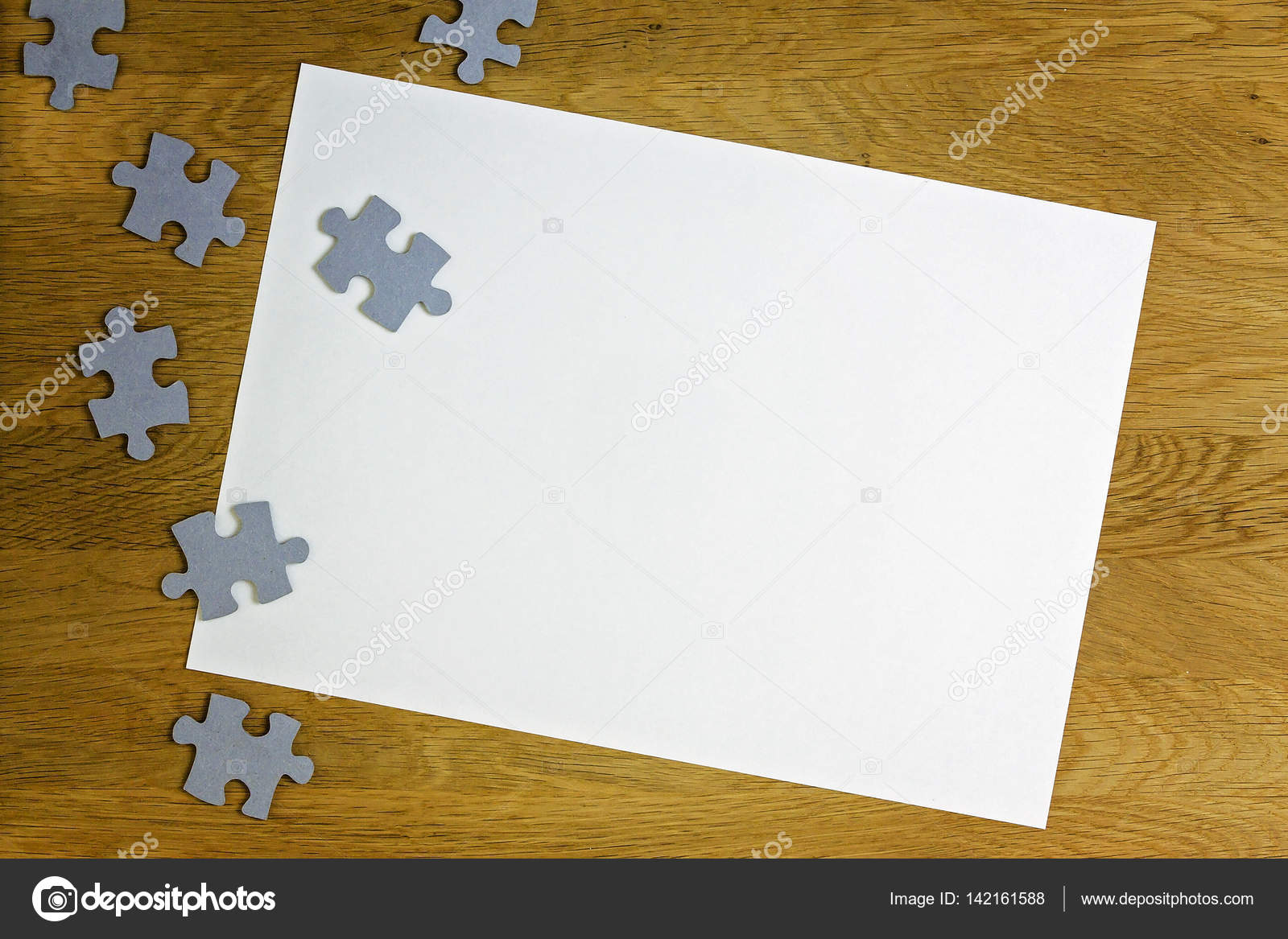 white blank sheet of paper surrounded by puzzle pieces on wooden