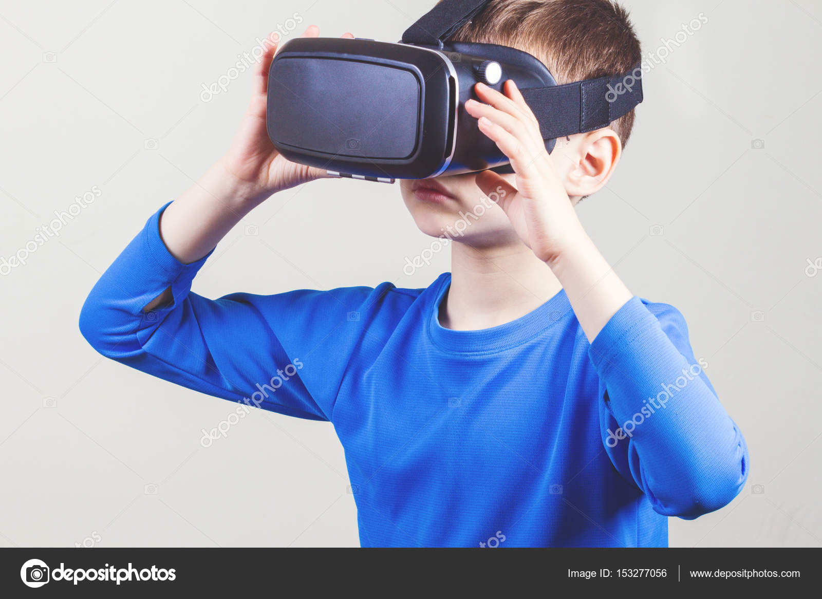 Little kid wearing virtual reality goggles watching movies