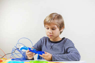 Focused child creating with 3d printing pen