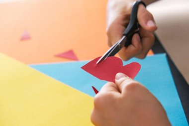 Paper crafts for kids. Child hands cutting colored paper with scissors at the table