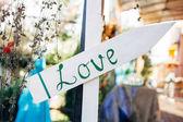 Bílý dřevěný šíp s slovo láska. Svatební koncept na rozostřeného pozadí