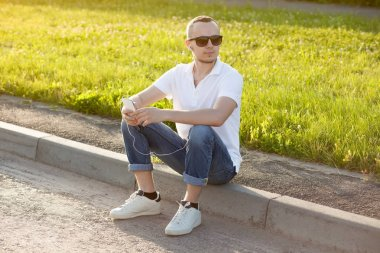 Young man wearing sunglasses sitting on curb and listening to music by modern smartphone
