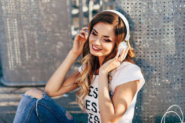 Closeup portrait of beautiful young woman in white T-shirt sitting under metal fence and listening music by headphones