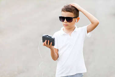 Closeup portrait of little boy in sunglasses and white t-shirt with vintage music player in hands