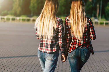 Two beautiful sisters twins walking in summer park. Back view of young blond ladies spending time together