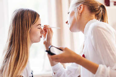 Female make up artist making make up to woman in beauty salon