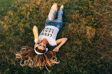 Woman lying on grass in headphones