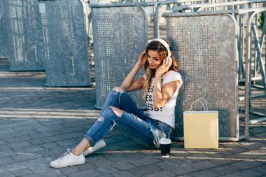 Woman in headphones on pavement
