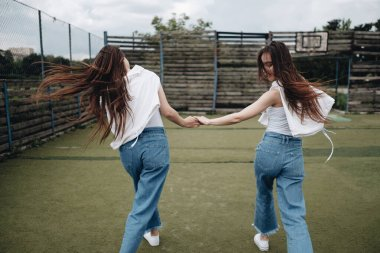 Portrait of Two Young Brunette Twins Sisters Dressed Alike in Jeans and White T-shirt, Best Friends Forever Concept