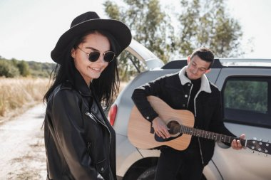 Happy Traveling Couple Dressed in Black Stylish Clothes Enjoying a Car Trip on the Field Road, Man Playing Guitar, Vacation Concept