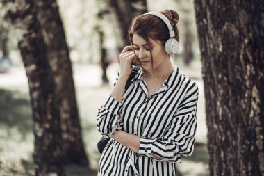 Outdoor Summer Portrait of Young Beautiful Girl in White Striped Stylish Dress Listens Music in Headphones