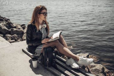 Outdoor Summer Portrait of Young Beautiful Girl in Black Leather Jacket and Glasses Reads the Book Near the Lake