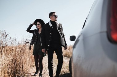 Happy Traveling Couple Dressed in Black Stylish Clothes Enjoying a Car Trip on the Field Road, Vacation Concept