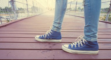 sneaker shoes and blue jeans on the bridge