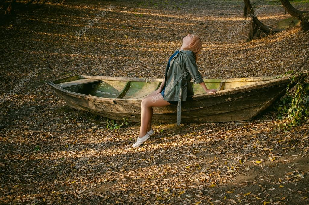 Pretty blonde sitting in a wooden old boat which is on the ground laid by yellow fallen autumn leaves