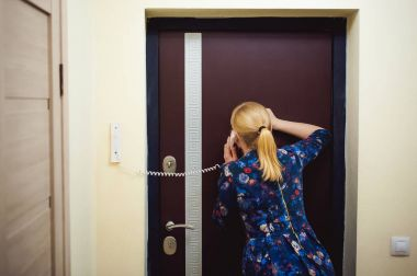 blonde woman answers the intercom call, hold the phone to his ear, waiting for the arrival of the long-awaited guest. Being in apartment near front door