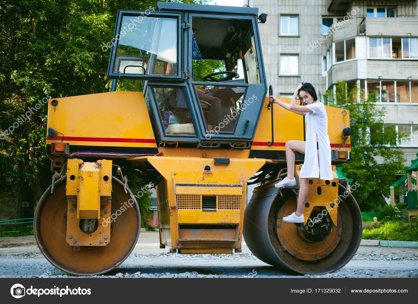 Young Woman With Bare Feet Dressed In White Sneakers And A Long Jersey Against A Backdrop Of Urban Landscapes And Road Machinery Asphalt Paver