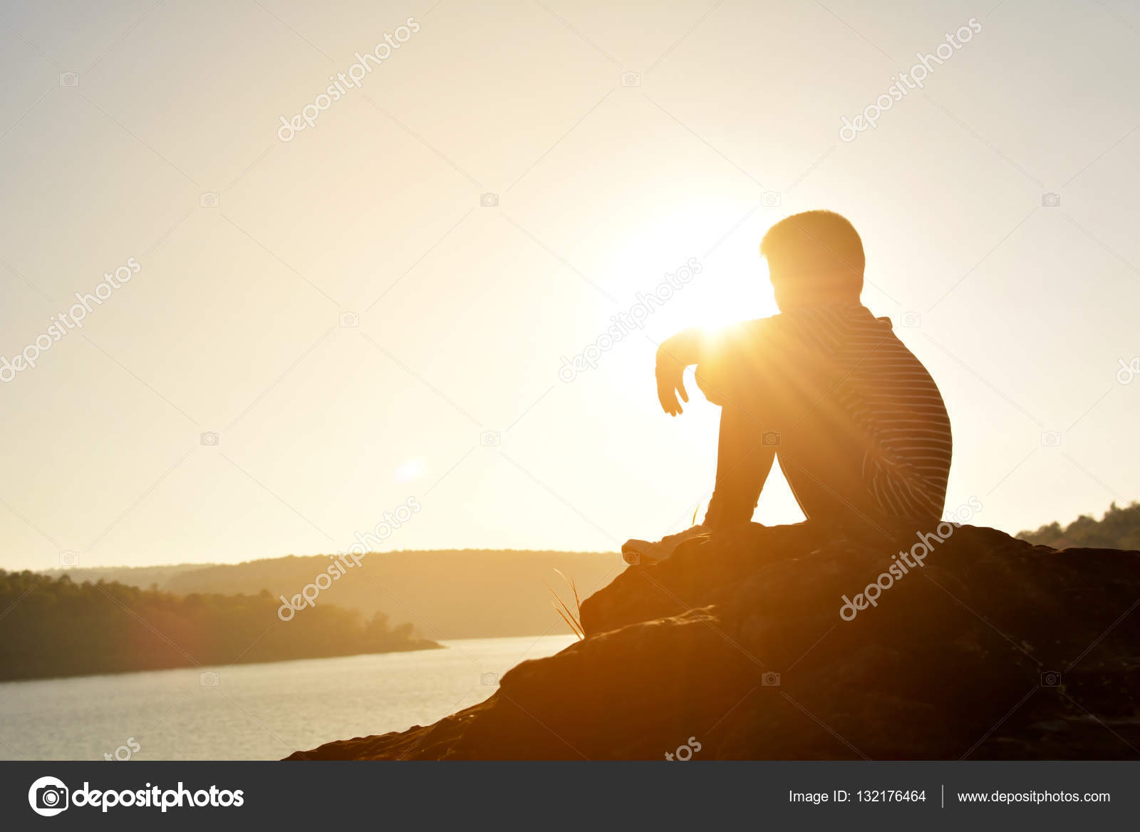 silhouette of sad boy and sitting on the rock in river at the sky