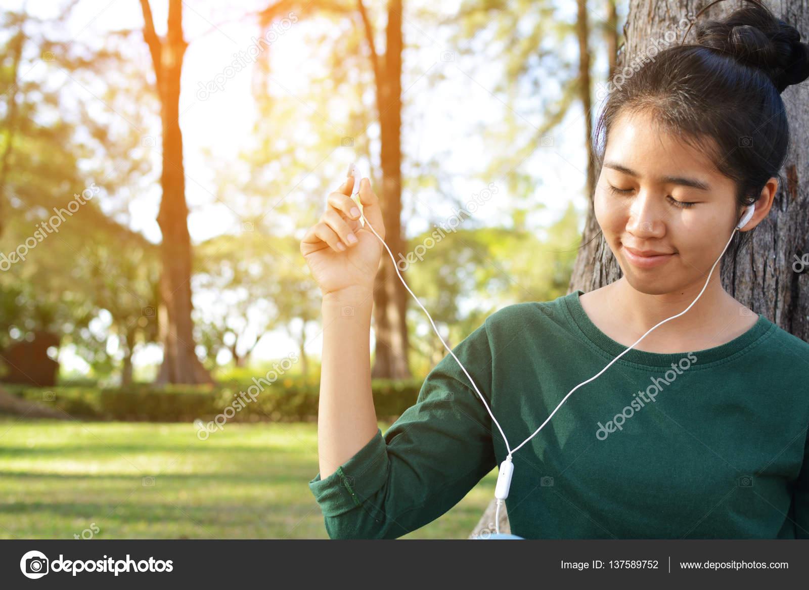 Happy women listen to music in smartphone tree nature