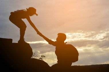 Silhouette of girl helps a boy on mountain