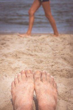Mans feet on the beach
