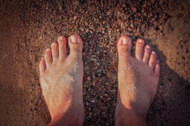 Mans feet on the seashore