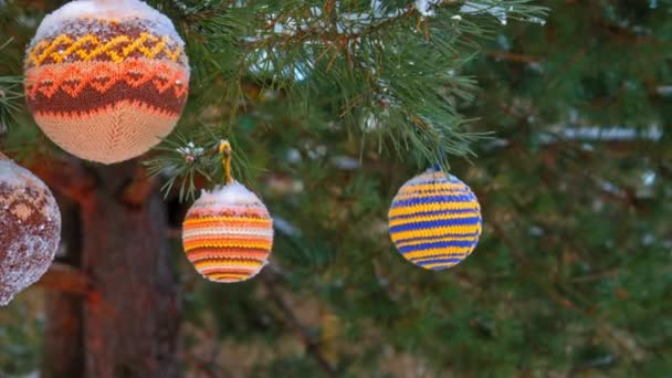 Christmas balls hanging on pine branches covered with snow