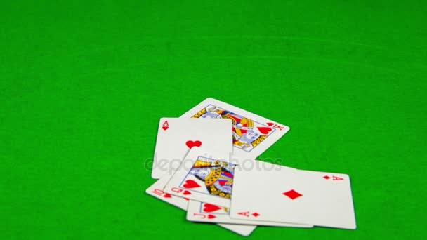 hrací karty padající na zeleném stole