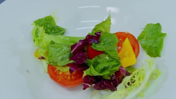 kuchař dává salát v misce