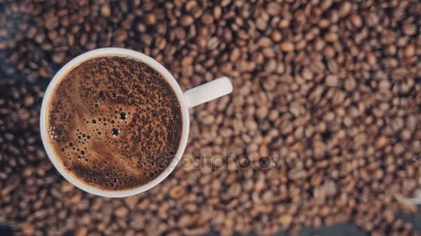hrnek s horkou kávou na pražených kávových zrn. Zpomalený pohyb
