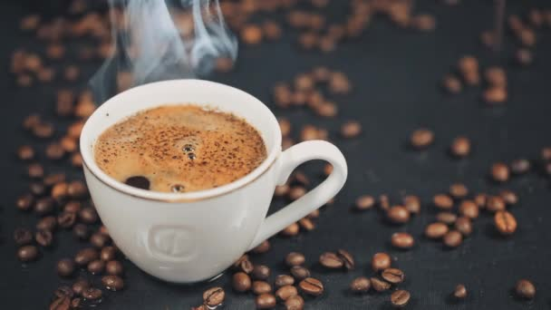 cup with hot drink on roasted coffee beans. Slow motion