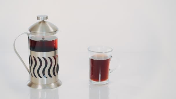 průhledné konvice s čajem a hrnek s horkým čajem na bílém pozadí