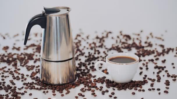 gejzír kávy, káva pohár a kávová zrna na bílém pozadí