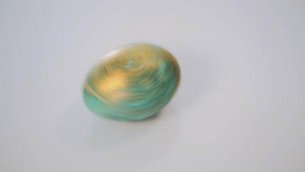 Piros és zöld húsvéti tojás forgatni, fehér háttér, lassú mozgás.
