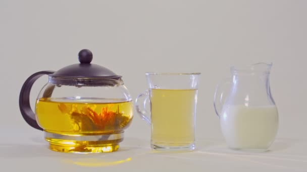 green tea in a glass teapot, the tea in a transparent Cup and a  jug of milk