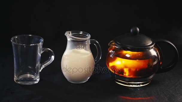 tea in a glass teapot, the tea in a transparent Cup and a small jug of milk